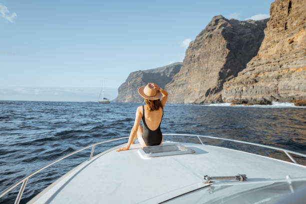 Woman sailing on the yacht near the rocky coast stock photo