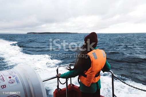 Woman going to penguin island through strong wind and cold in Chile