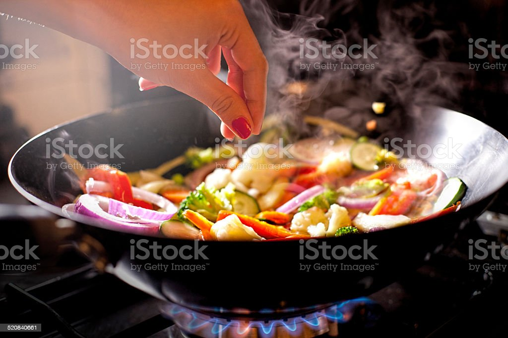 Woman salting her meal stock photo