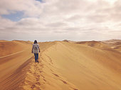 Rear view of a mid age woman walking on top of a Sand dune with clouds in the sky at Dune 7 Walvis Bay Swakopmund Namibia Africa