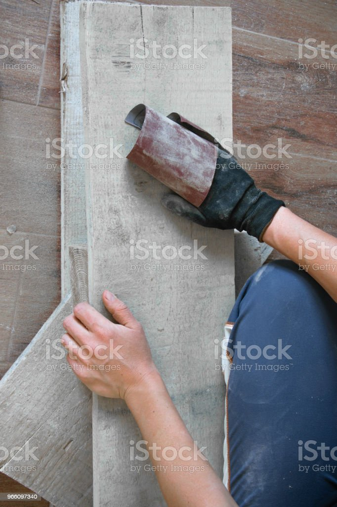 Woman sand with fine sandpaper a wooden table indoor. Repair, DIY concept - Royalty-free Adulto Foto de stock