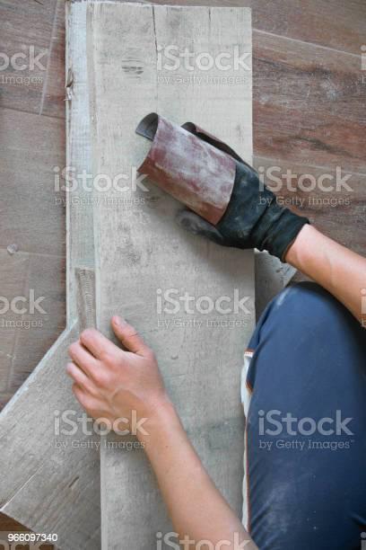 Woman Sand With Fine Sandpaper A Wooden Table Indoor Repair Diy Concept - Fotografias de stock e mais imagens de Adulto
