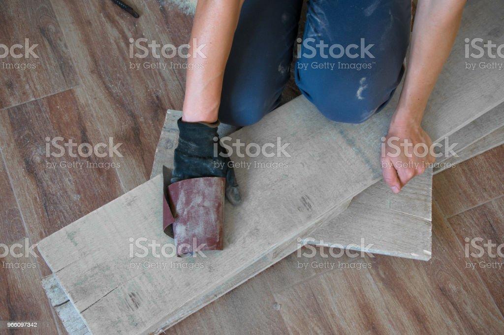 Kvinna slipa med fint sandpapper ett träbord inomhus. Reparation, DIY koncept - Royaltyfri Albanien Bildbanksbilder