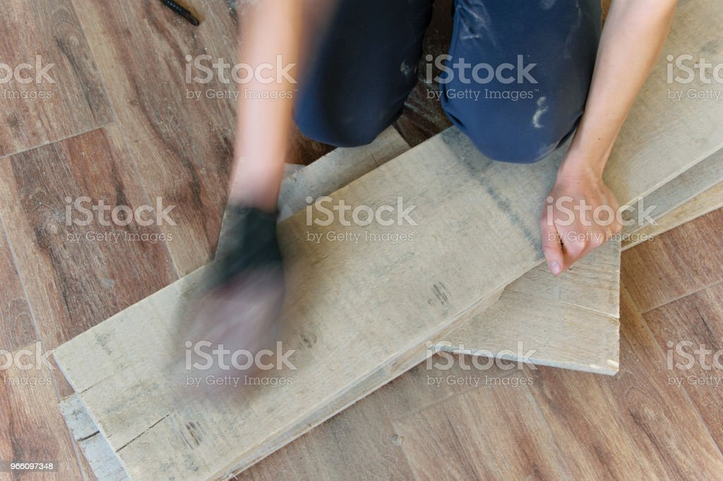 Woman sand with fine sandpaper a wooden table indoor. Repair, DIY concept - Royalty-free Adult Stock Photo