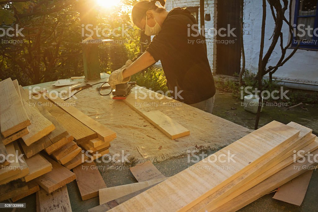 DIY - woman sanding wood planks with sand machine stock photo
