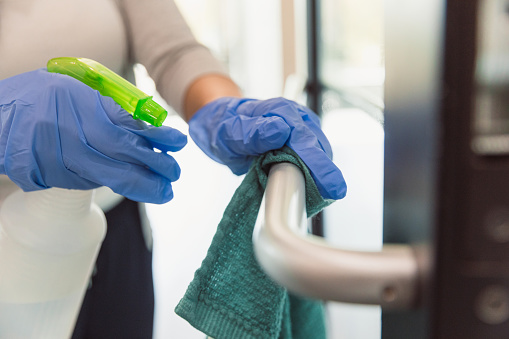 A female custodian wears protective gloves as she cleans a hand rail in an office during COVID-19