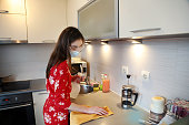 Young woman sanitizing to prevent germs and bacteria infections in the kitchen