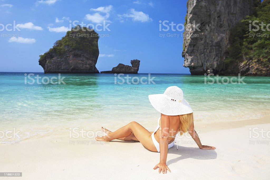Woman sat on shoreline of beach wearing white bikini and hat stock photo