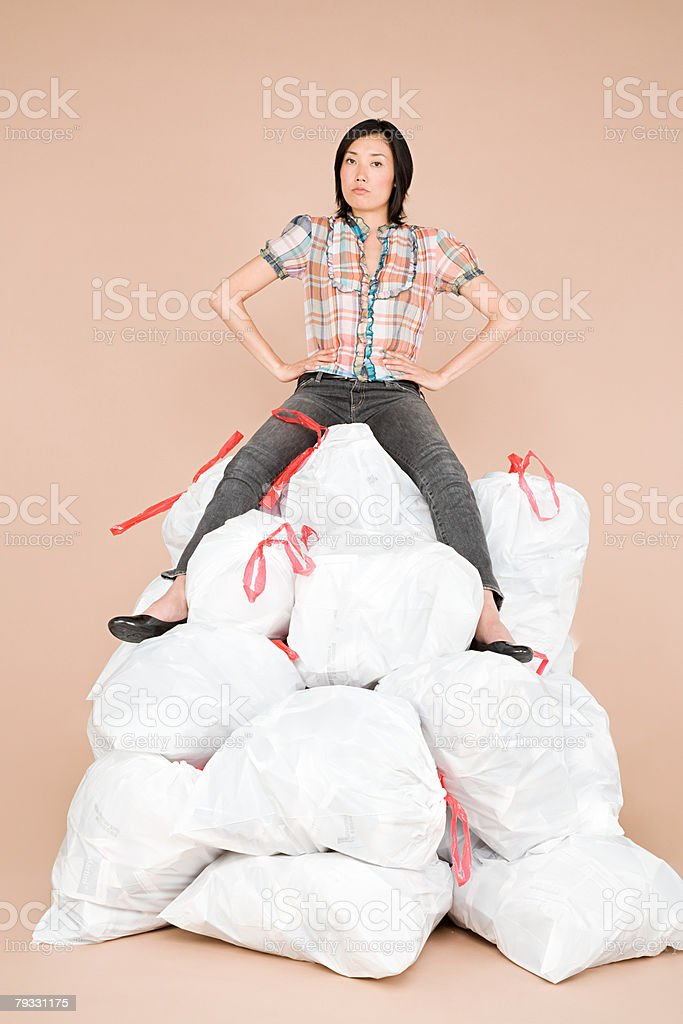 A woman sat on top of a pile of rubbish bags 免版稅 stock photo