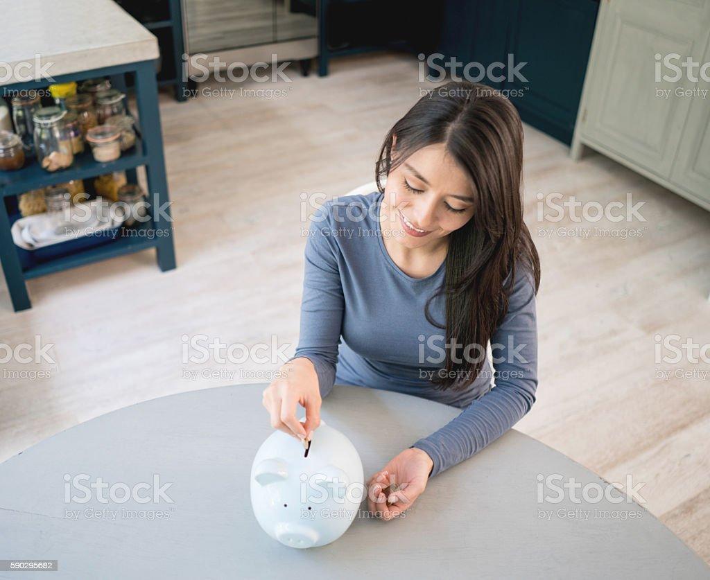 Woman saving money in a piggybank royaltyfri bildbanksbilder