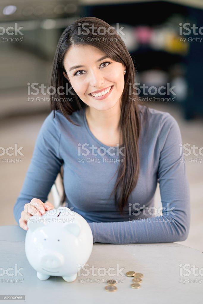 Woman saving money in a piggybank Стоковые фото Стоковая фотография