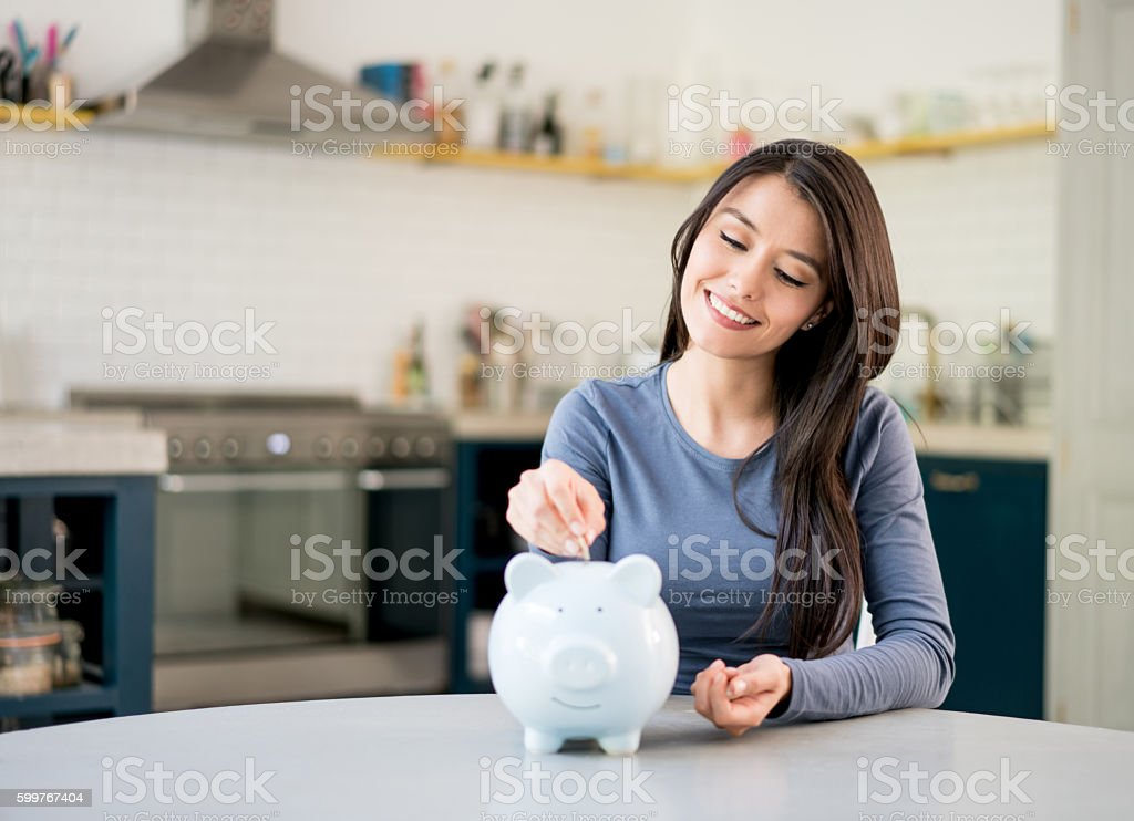 Woman saving money in a piggybank stock photo