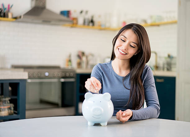 Woman saving money in a piggybank - Photo