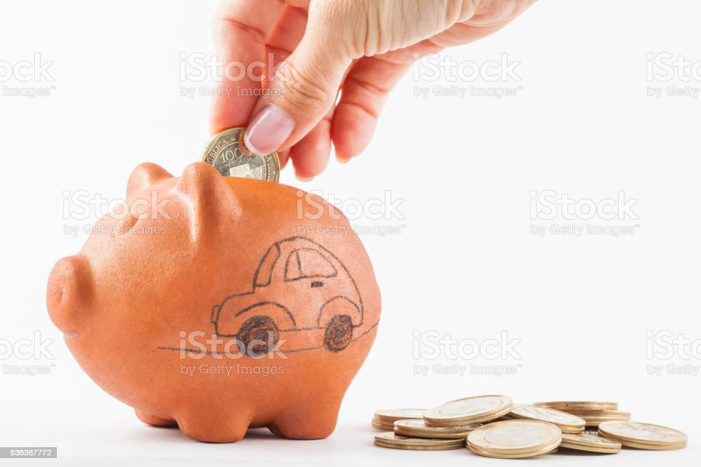 Woman saving money into a traditional clay piggy bank for a car stock photo