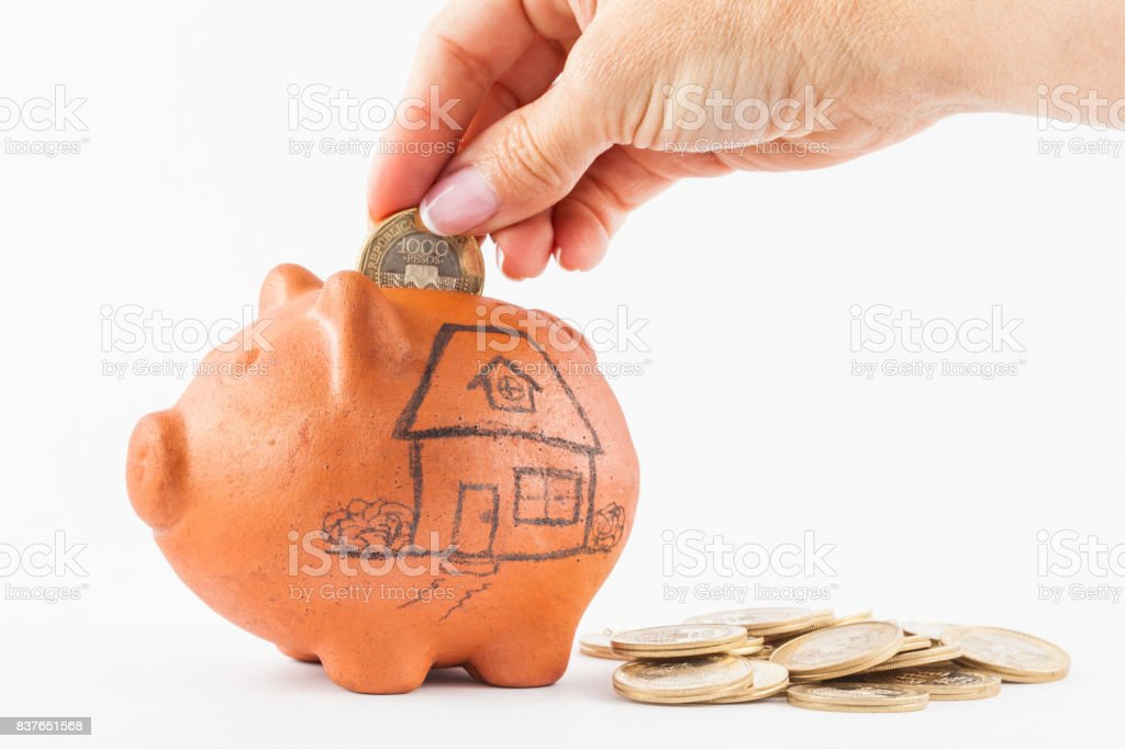 Woman saving money into a traditional clay piggy bank for a house stock photo