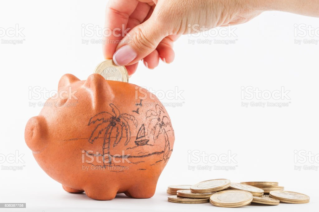 Woman saving money into a traditional clay piggy bank for holidays stock photo