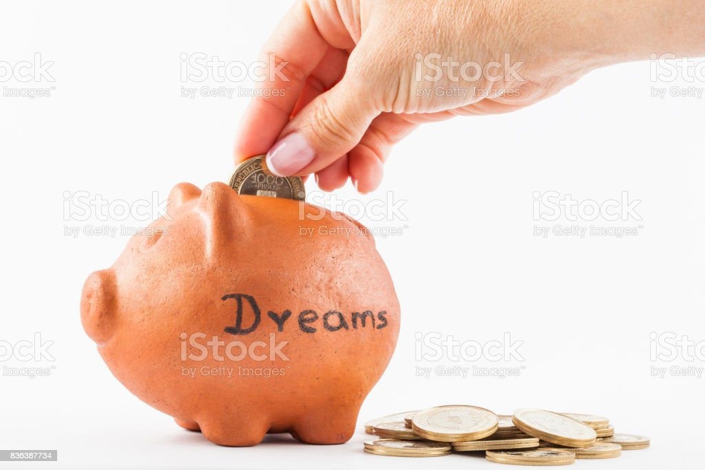 Woman saving money into a traditional clay piggy bank to achieve dreams stock photo