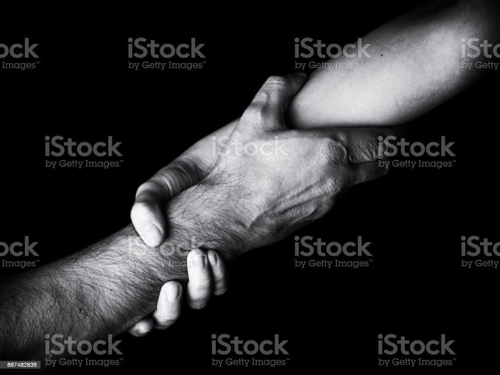 Woman saving, rescuing and helping man by holding or griping the forearm. stock photo