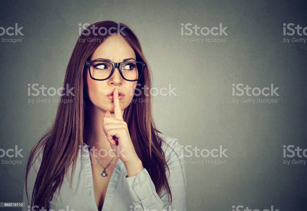 Woman saying hush be quiet with finger on lips gesture stock photo