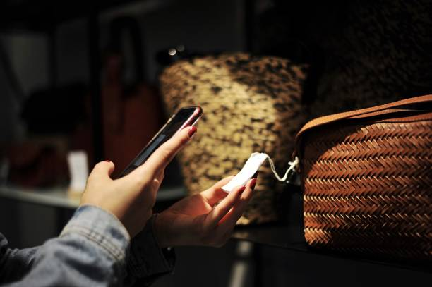 Woman scanning a barcode at a shop for a bag stock photo