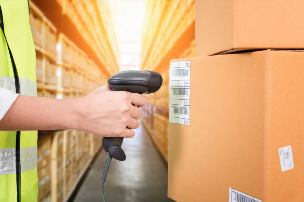 Woman scanning barcode from a label in modern warehouse stock photo