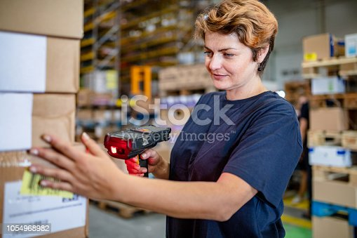 istock Woman scanning boxes in warehouse 1054968982