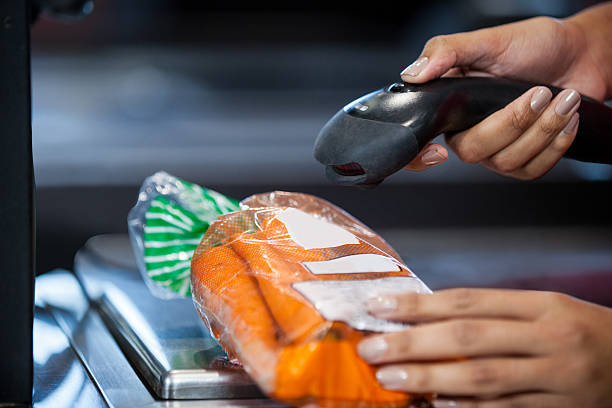 Woman scanning goods at checkout counter stock photo