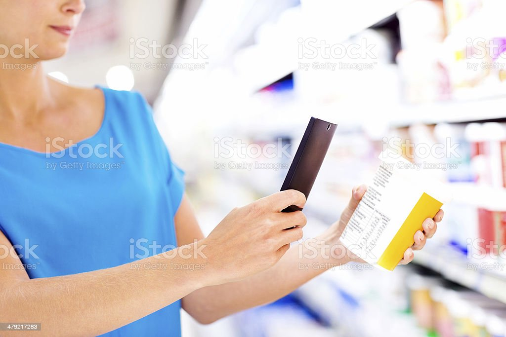 Woman Scanning Product Barcode On Smart Phone In Supermarket stock photo