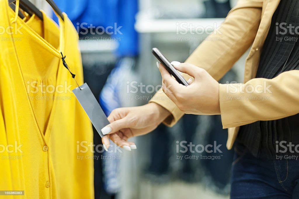 Woman scanning QR code in shopping mall stock photo