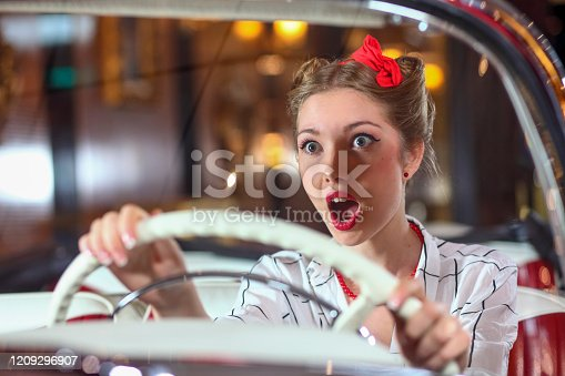 Woman driving through city at nigh scared by what is happening in front.