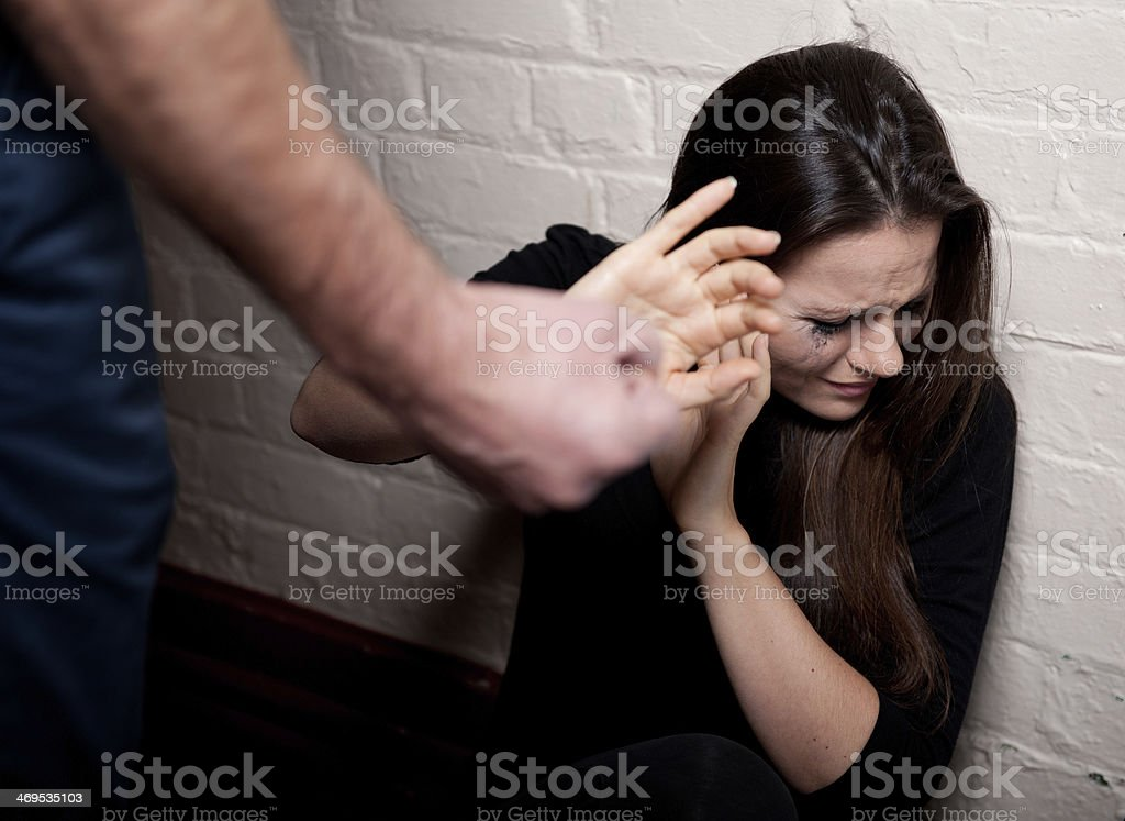 A woman scared of a man who is about to hit her stock photo