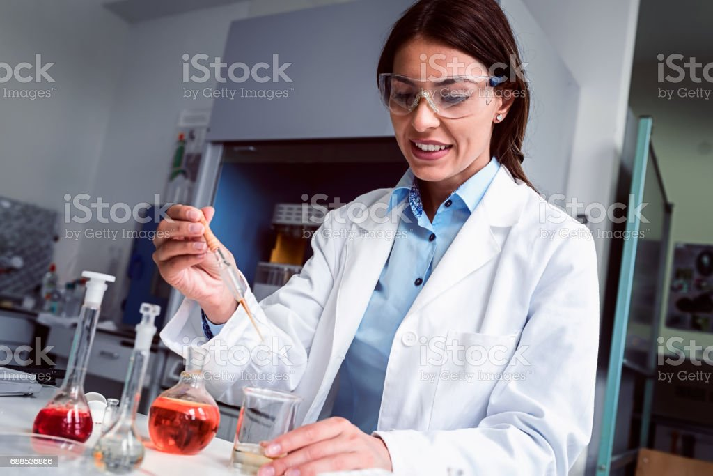 Woman scientist carrying out experiment in research laboratory. Medical chemist lab. stock photo