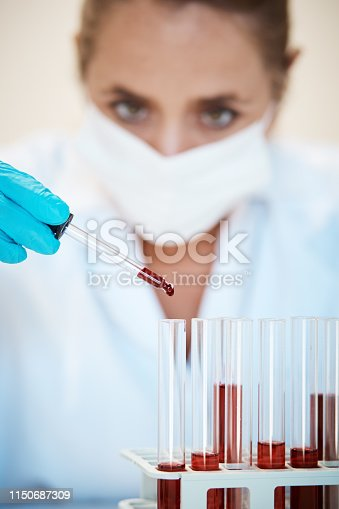 A woman scientist in lab coat, gloves, and mask, carefully drips blood from a pipette into test tubes.