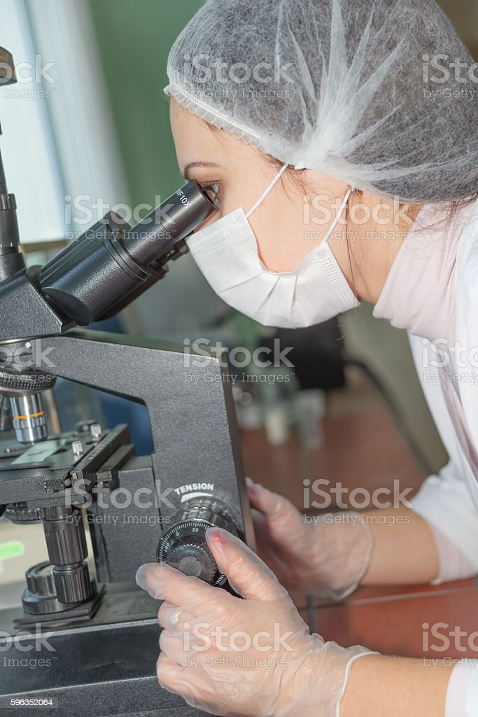 Woman scientist looking in a microscope royalty-free stock photo