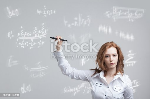 istock Woman scientist or student working with various high school maths and science formula 802316928