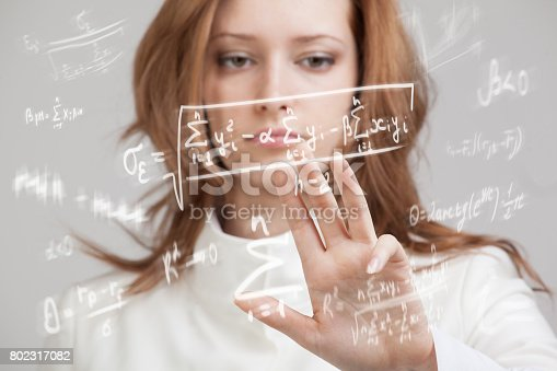 istock Woman scientist or student working with various high school maths and science formula 802317082