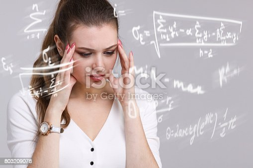 istock Woman scientist or student working with various high school maths and science formula 803209078