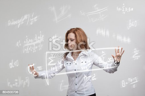 istock Woman scientist or student working with various high school maths and science formula 804500706