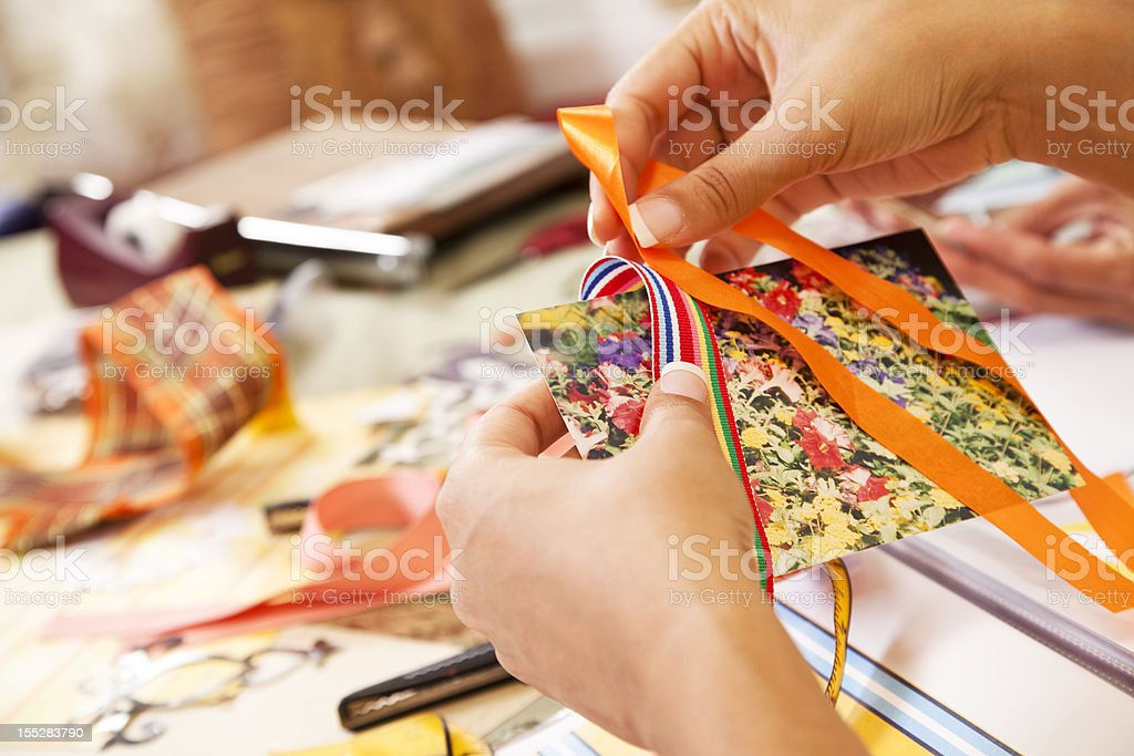 Woman scrapbooking, crafts. Ribbons for trim on photograph. stock photo