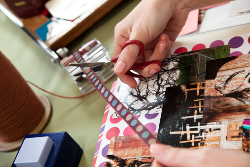 Lady scrapbooking, cutting trim and arranging images.