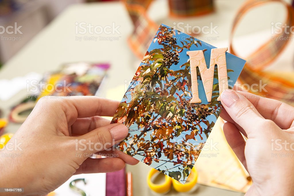 Woman scrapbooking, letter M on photograph. Art, craft, hobby. stock photo