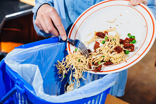Woman scraping food leftovers into bin stock photo