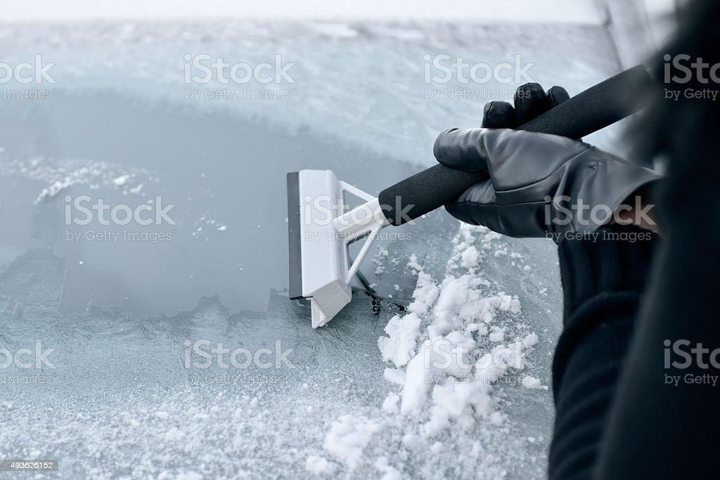 Woman Scraping Ice from a Windshield stock photo