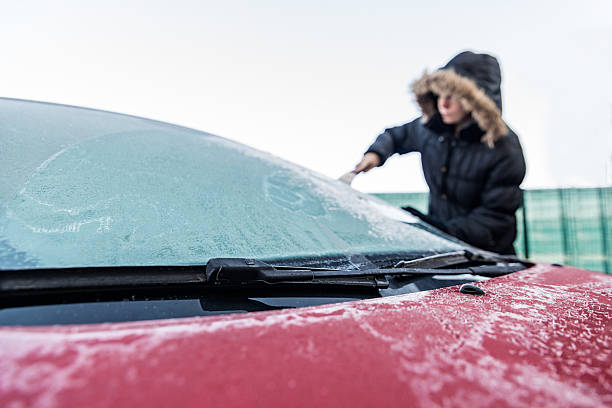 Woman scraping ice from car windscreen stock photo