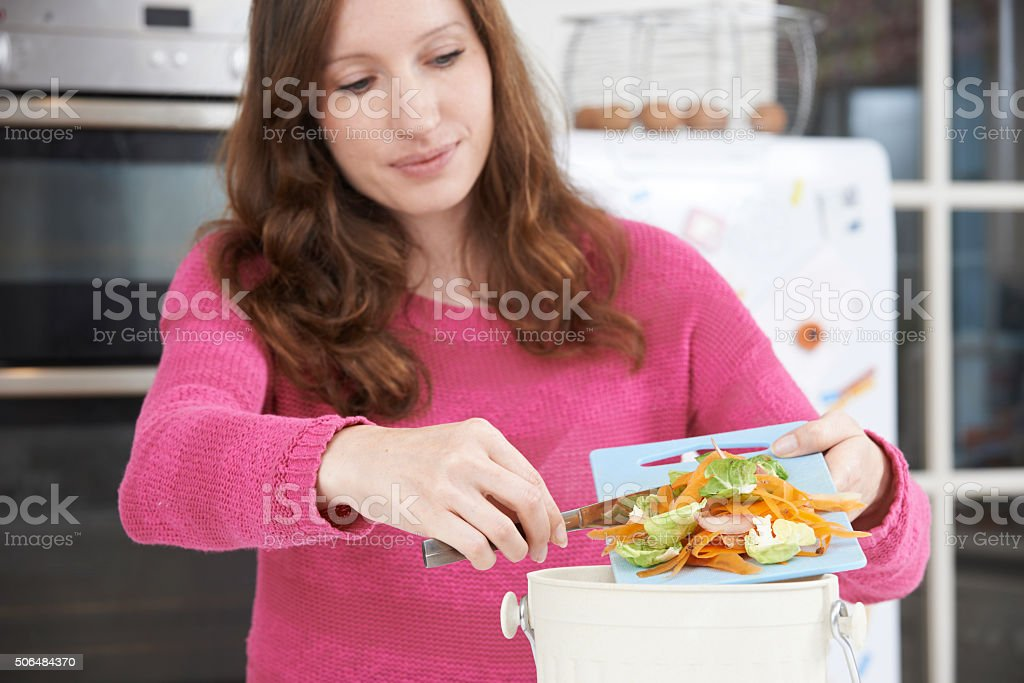 Woman Scraping Vegetable Peelings Into Recycling Bin stock photo