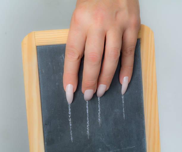frau kratzt ihr schiefer mit ihren langen nägeln - nails stiletto stock-fotos und bilder