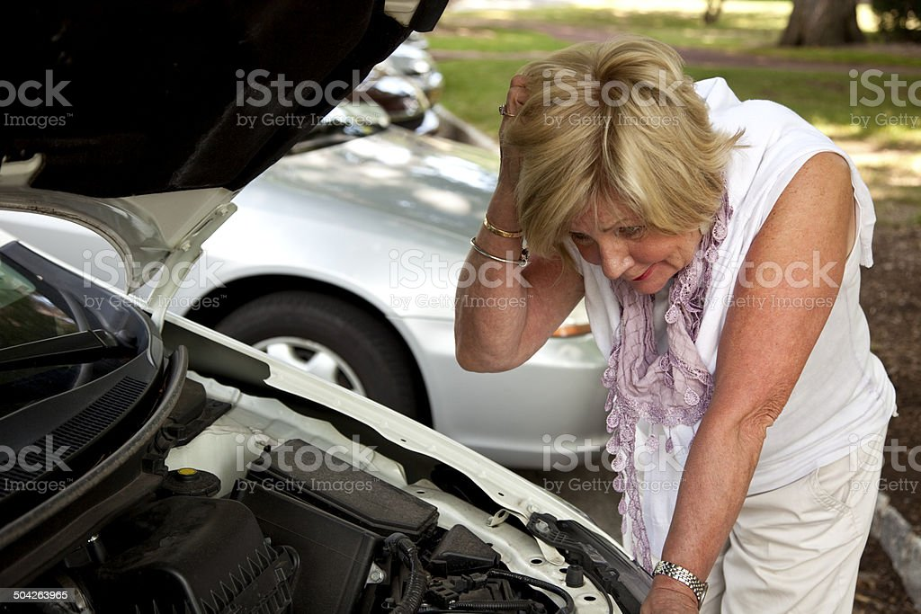 Woman scratching head with broken down car royalty-free stock photo