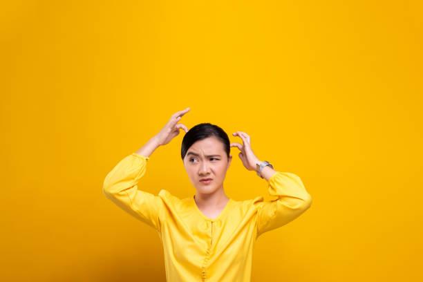frau kratzt ihren kopf isoliert über gelbem hintergrund - trockene kopfhaut was tun stock-fotos und bilder