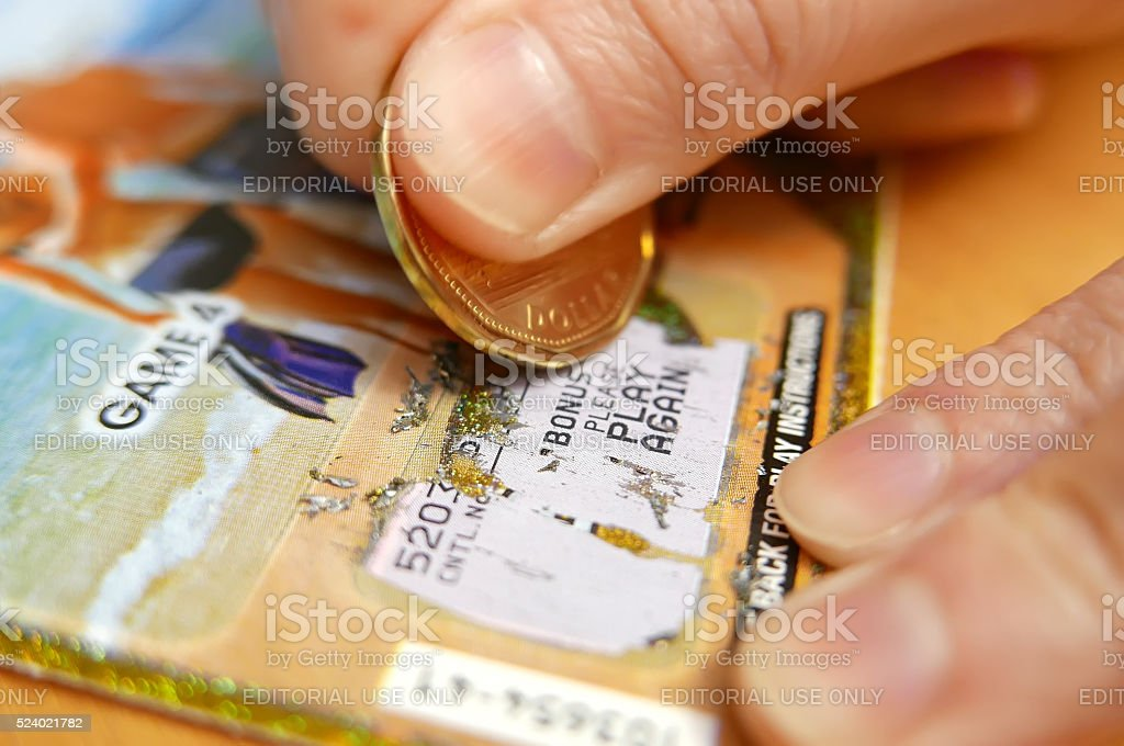 Woman scratching lottery ticket stock photo