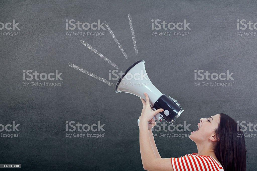 Woman Screaming in Megaphone on blackboard stock photo
